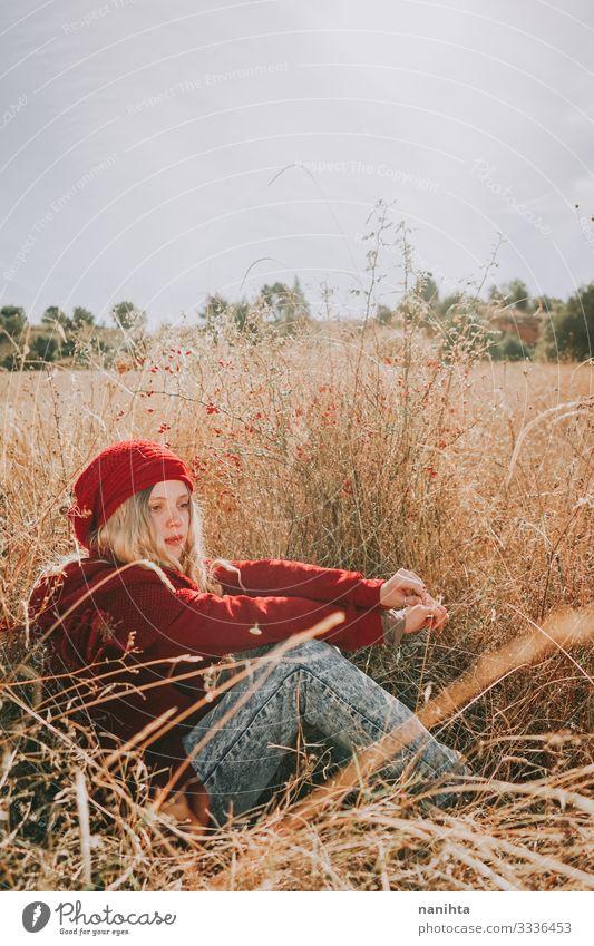 Junge Frau auf einem Feld an einem sonnigen Tag in roter Kleidung Sinnesorgane Windstille Sommer Mensch feminin Jugendliche Erwachsene 1 18-30 Jahre Natur