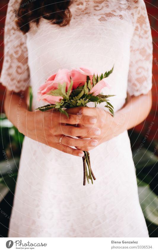 Braut hält ihren kleinen Hochzeitsstrauß aus rosa Rosen feminin Frau Erwachsene Pflanze Blumenstrauß Liebe Zusammensein Romantik Farbe Idee Ordnung Tradition