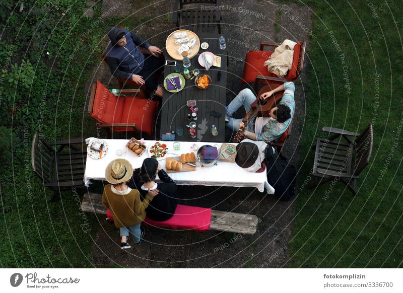 Blick von oben auf vier Menschen mit Picknick und Gitarrenspieler am Gartentisch chillen Zusammensein ruhig Gemeinschaft Siesta Gartenidylle Gitarre spielen