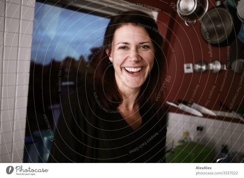 Junge Frau lacht in der Küche Messer Pfanne Fenster Lifestyle Freude schön Leben Häusliches Leben Wohnung Jugendliche Gesicht Grübchen 18-30 Jahre Erwachsene