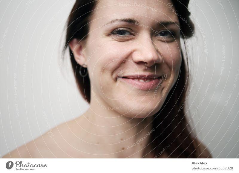 Portrait einer lächelnden jungen Frau vor weißer Wand Freude Glück schön Leben harmonisch Wohlgefühl Junge Frau Jugendliche Gesicht 18-30 Jahre Erwachsene