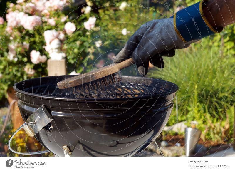 Grill reinigen. Männliche Hand mit Handschuhen säubert runden Grill mit Bürste. Vorbereitung eines Grills vor dem Kochen. Mann putzt einen Grill im Garten