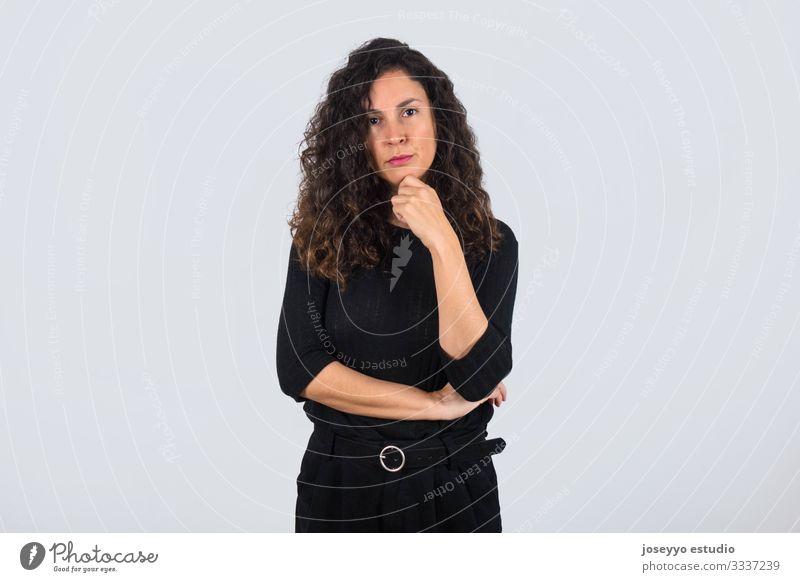 Lockenhaarige brünette Frau in Schwarz mit der Hand am Kinn, die mit ernstem Ausdruck in die Kamera schaut. 30-40 Jahre Inserat Einstellung Hintergrund schön