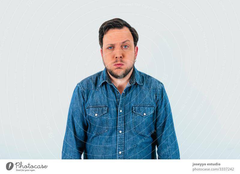 Junger Mann mit Ausdruck von Müdigkeit und Jeanshemd. Vereinzelter grauer Hintergrund. 30-40 Jahre Inserat Werbung Gleichgültigkeit Einstellung Transparente
