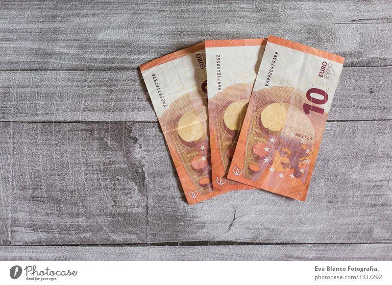 Drei Zehn-Euro-Schein. Euro-Banknoten auf grauem Holzgrund. Das Geldkonzept Vermögen Stapel Hinweis Einkommen Löhne Gehalt zählen verkaufen Erträge Anhäufung