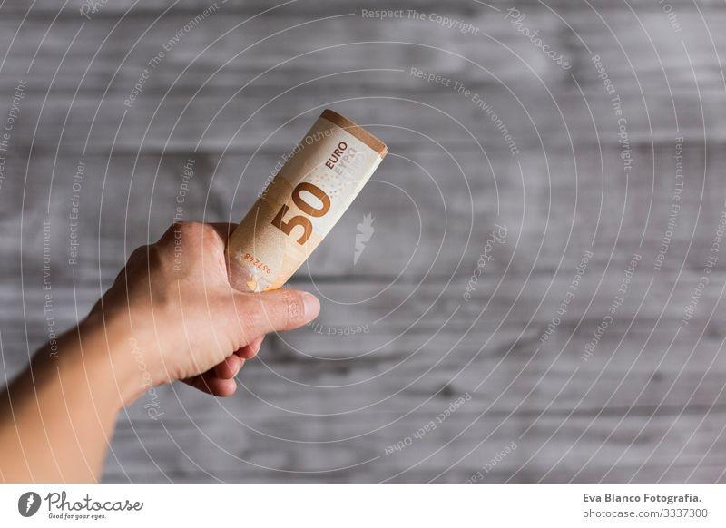 Frau hält isoliert auf grauem Holzuntergrund Bargeld in der Hand. Fünfzig Euro-Scheine. Europäer Geld Europa fünfzig Vermögen Halt Zahlung finanziell
