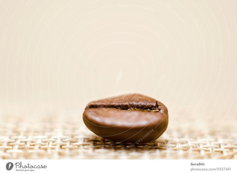 ein Korn Kaffee auf einem Mattierungsmakro Frühstück Stoff dunkel frisch natürlich braun schwarz Energie Farbe aromatisch Hintergrund Bohnen beige Unschärfe
