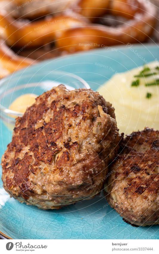 Fleischpflanzerl auf einem Teller Abendessen Gastronomie Wärme Holz lecker saftig blau braun Pflanzerl Fleischklösse fleischpflanzerl Kartoffelpüree püriert