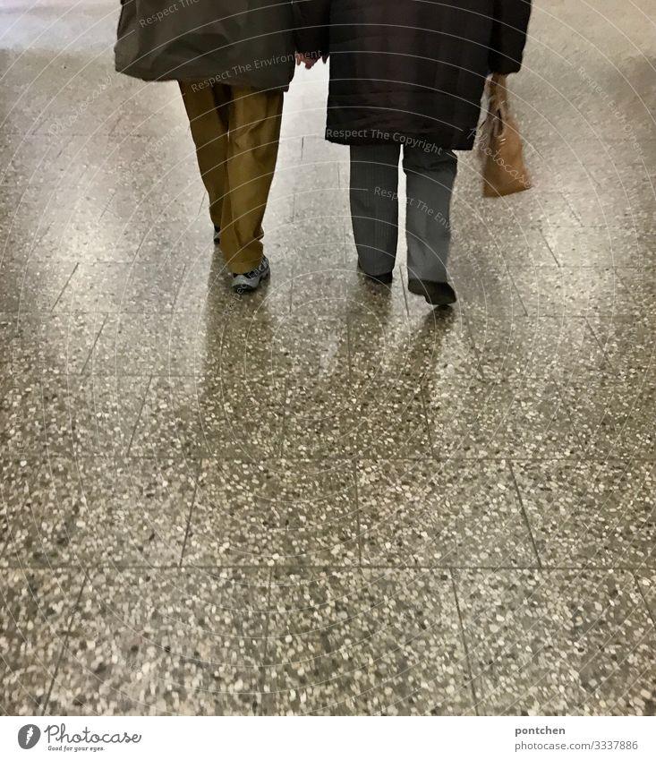Liebe-Zwei Senioren gehen Hand in Hand  über bodenfließen Mensch maskulin feminin Weiblicher Senior Frau Männlicher Senior Mann Partner 2 60 und älter Fürsorge