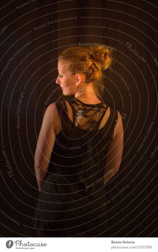 junge Frau im Spitzentop schaut im Abendlicht von hinten über die linke Schulter hübsch schwarzer Hintergrund Blick attraktiv verführerisch Porträt