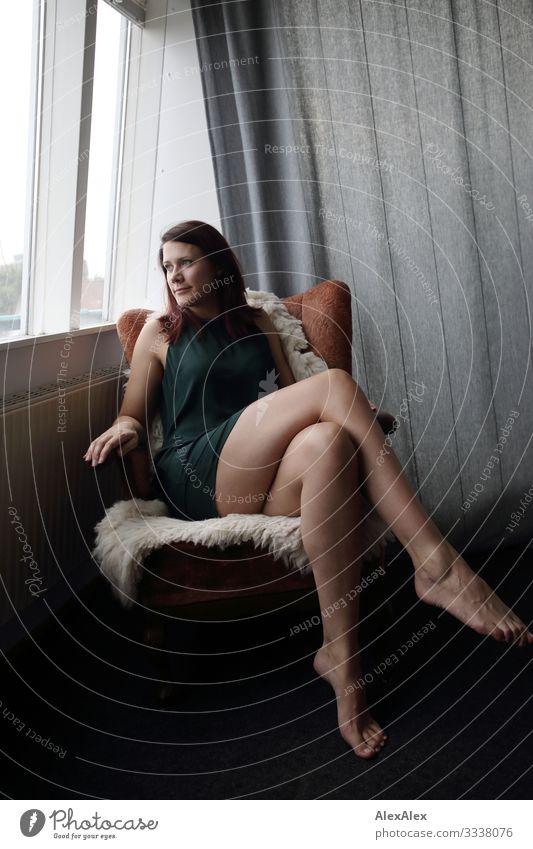 Portrait einer langbeinigen jungen Frau, die in einem Sessel sitzt und aus dem Fenster schaut Lifestyle elegant Stil schön Wohlgefühl Häusliches Leben Wohnung
