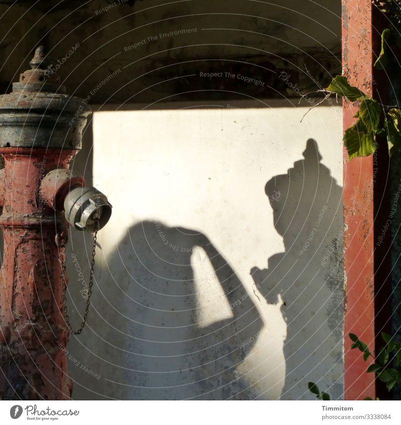 Teilansicht eines Hydranten, nachdenklich in die Betrachtung seines Schattens und den einer Fotografin versunken alt rostig Hintergrund neutral Fläche Metall