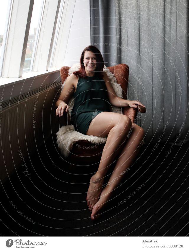 Portrait einer jungen langbeinigen Frau, die lächelnd in einem Sessel sitzt Lifestyle elegant Freude schön Leben Wohlgefühl Häusliches Leben Wohnung Wohnzimmer