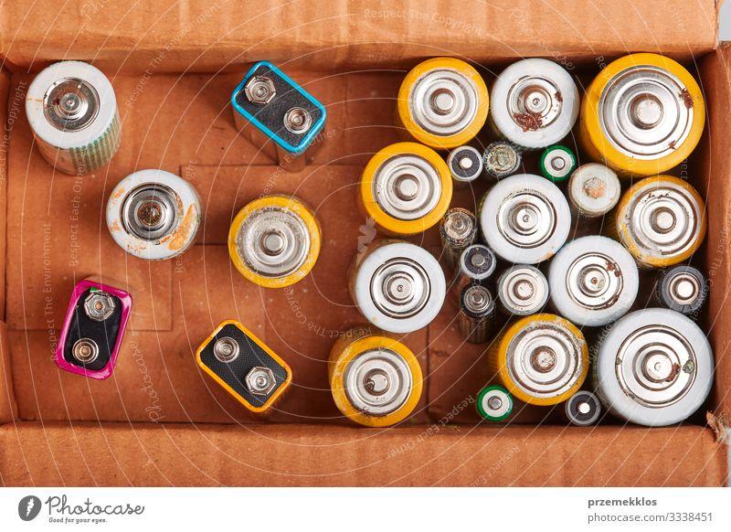 Entladene Batterien in einem Karton. Sammeln von gebrauchten Batterien zum Recycling. Abfallentsorgung und Recycling. Kopierplatz für Text Umwelt alt grün