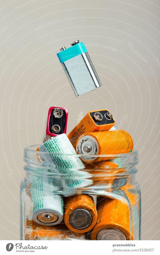 Gebrauchte Batterie, die in ein mit entladenen Batterien gefülltes Glas fällt Umwelt alt grün Energie Fürsorge Umweltverschmutzung Umweltschutz Recycling