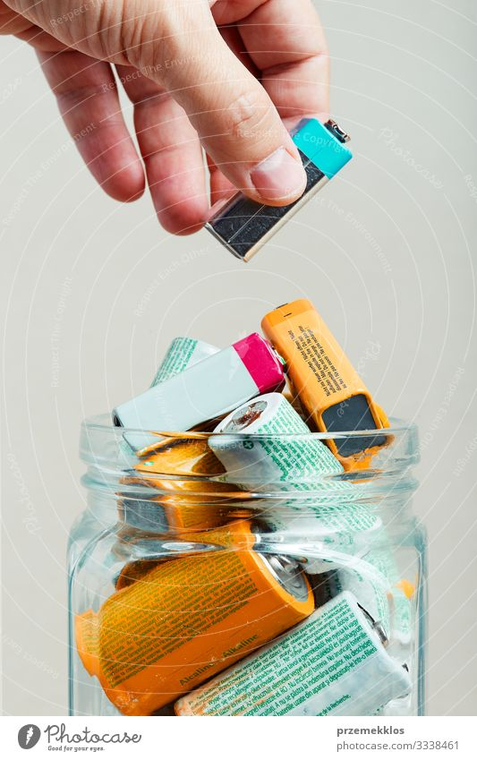 Männliche Hand legt gebrauchte Batterie in ein Glas mit entladenen Batterien Mann Erwachsene Umwelt alt grün Energie Fürsorge Umweltverschmutzung Umweltschutz