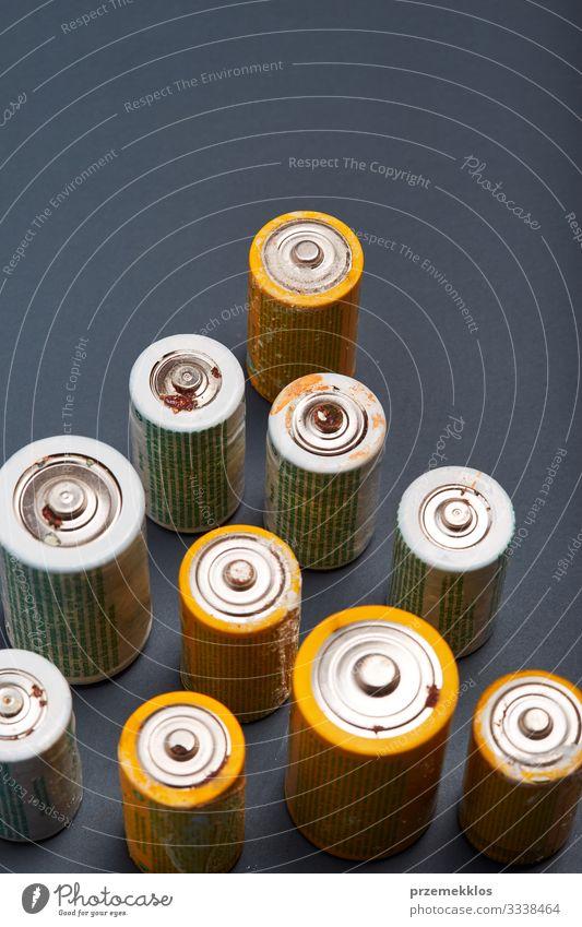 Entladene Batterien auf Papierhintergrund. Sammeln von gebrauchten Batterien zum Recycling. Abfallentsorgung und Recycling. Kopierplatz für Text Umwelt alt grün