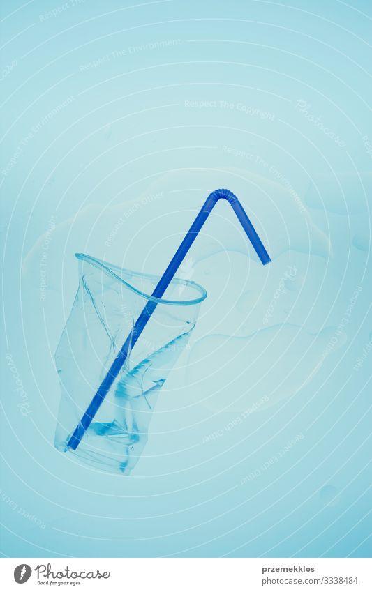Zerdrückter Plastikbecher und Trinkhalm auf blauem Hintergrund sparen Umwelt Container Kunststoff Umweltverschmutzung Müll wiederverwerten Recycling ökologisch