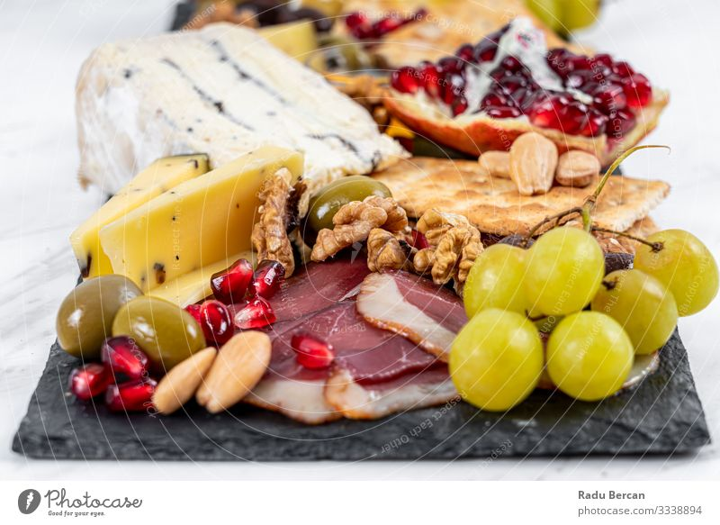 Speiseteller mit Trüffelkäse, Entenbrust, Briekäse, Pekannüssen, Granatapfelkernen, Trauben, Mandeln, Honig, Oliven und Crackern auf weißem Marmorhintergrund