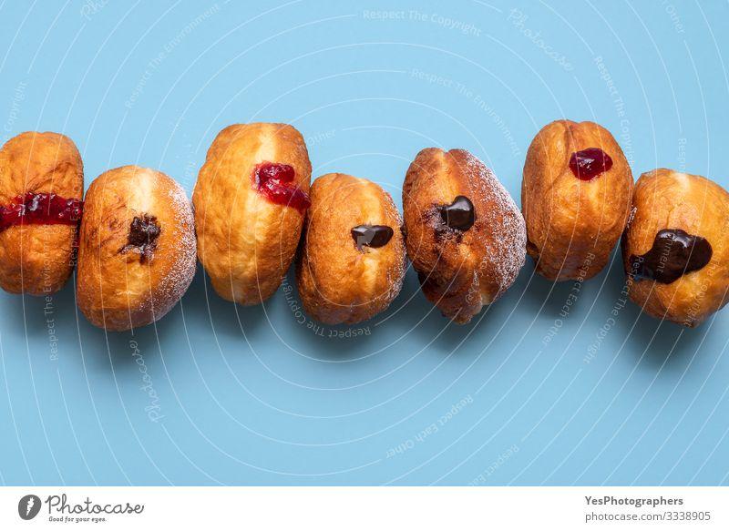 Hausgemachte Donuts in einer Reihe. Berliner Donuts mit Schokolade Kuchen Dessert Süßwaren Marmelade lecker Tradition Deutschland obere Ansicht Bäckerei