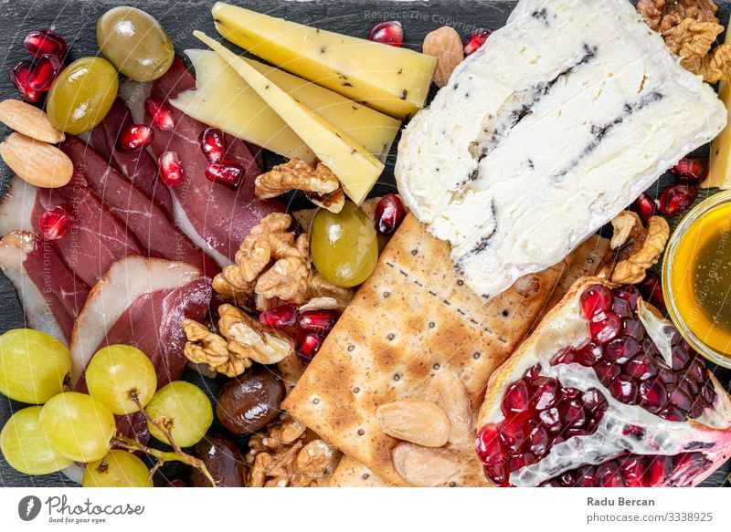 Speiseteller mit Trüffelkäse, Entenbrust, Briekäse, Pekannüssen, Granatapfelkernen, Trauben, Mandeln, Honig, Oliven und Crackern Weintrauben Saatgut Käse Platte