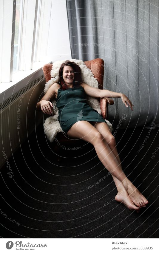Junge, langbeinige Frau liegt in einem Sessel und lacht Stil Freude schön Leben Häusliches Leben Wohnung Junge Frau Jugendliche Beine 18-30 Jahre Erwachsene