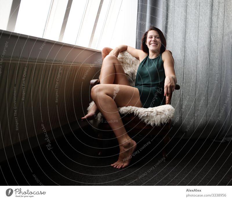 jungen große Frau sitzt schräg in einem Sessel und lacht Stil Freude schön Leben Häusliches Leben Wohnung Junge Frau Jugendliche Beine 18-30 Jahre Erwachsene