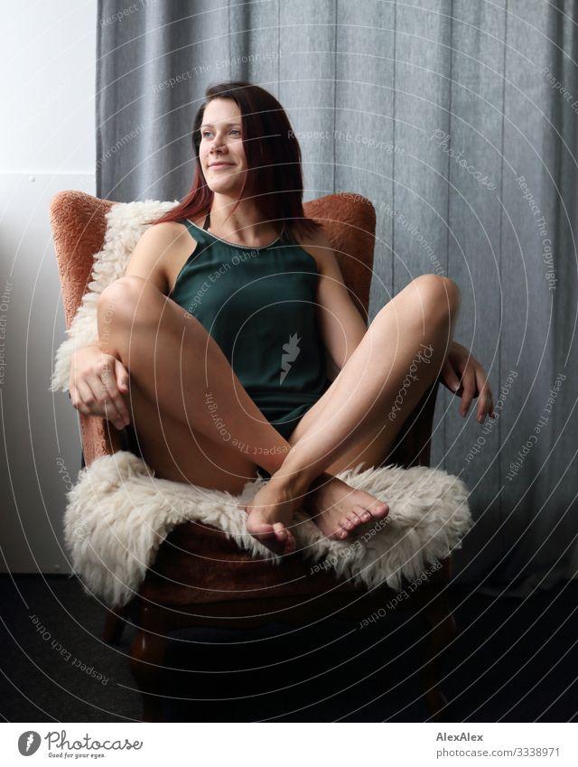 Junge große Frau sitzt in einem Sessel elegant Freude schön Leben Häusliches Leben Wohnung Wohnzimmer Junge Frau Jugendliche Beine 18-30 Jahre Erwachsene Kleid