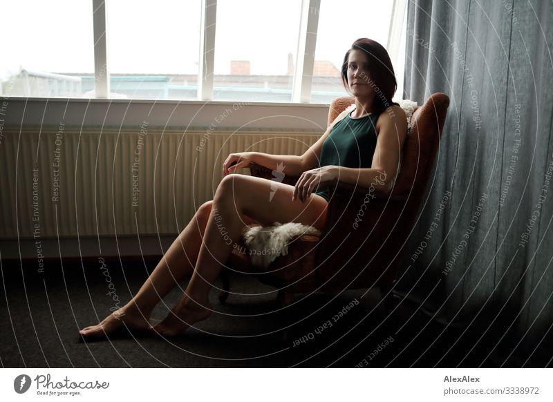 junge große Frau sitzt im Sessel vor dem Fenster elegant Stil schön Wohlgefühl Häusliches Leben Wohnung Wohnzimmer Junge Frau Jugendliche Beine 18-30 Jahre