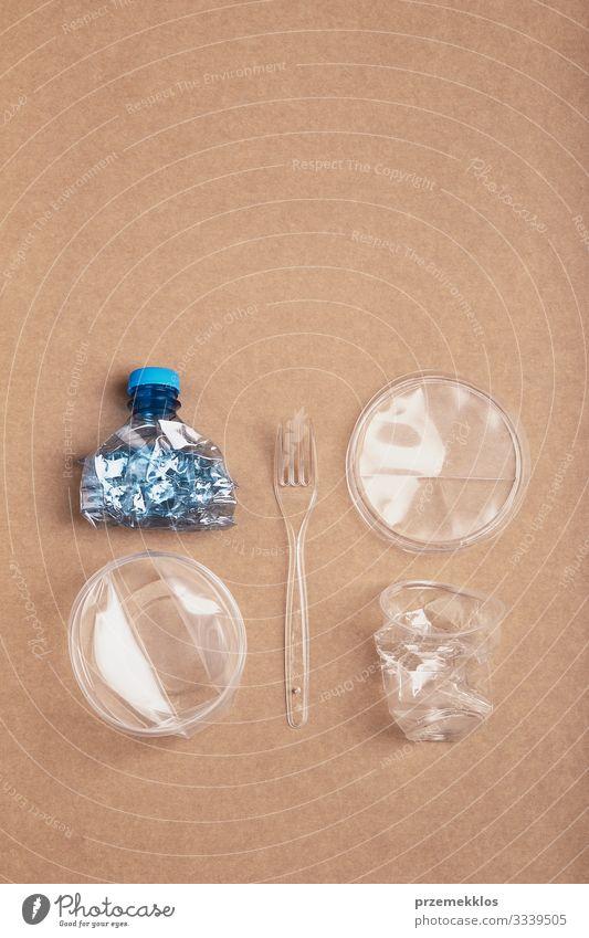 Zerquetschte Plastikflasche, Schachtel, Becher und Gabel über Karton Flasche sparen Umwelt Container Verpackung Kunststoffverpackung Kristalle blau