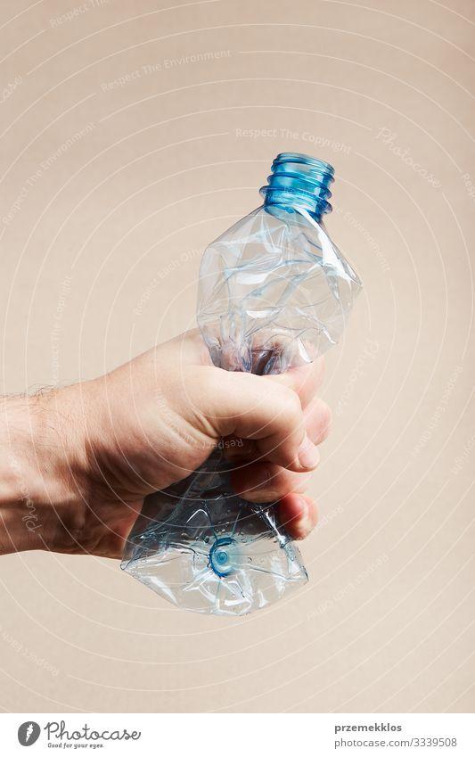 Männliche Hand hält gequetschte Plastikflasche Flasche sparen Mann Erwachsene Umwelt Container Kunststoff blau Umweltverschmutzung Müll wiederverwerten