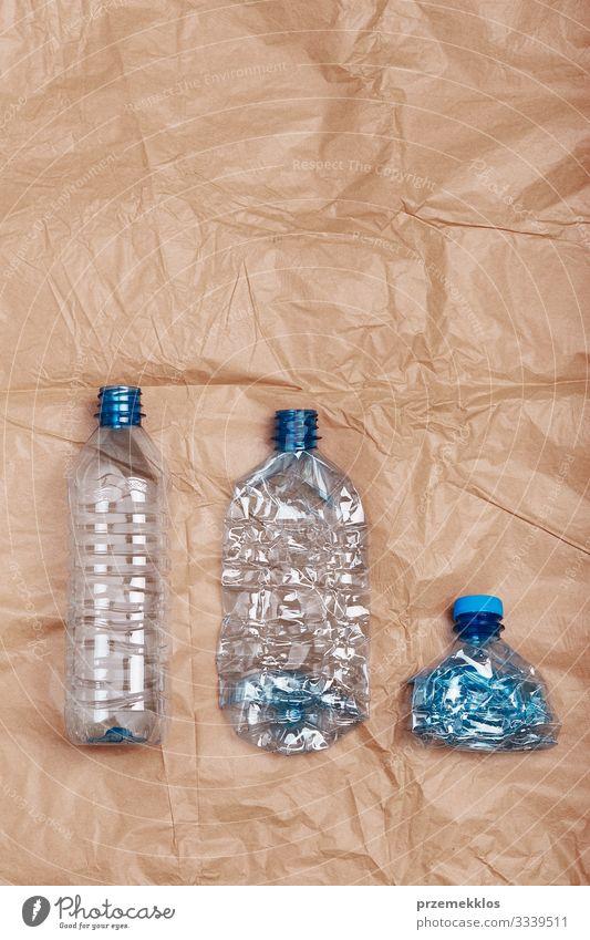 Zerquetschte leere Plastikflaschen in eine Reihe gestellt Flasche sparen Umwelt Container Papier Kunststoff blau braun Umweltverschmutzung Umweltschutz