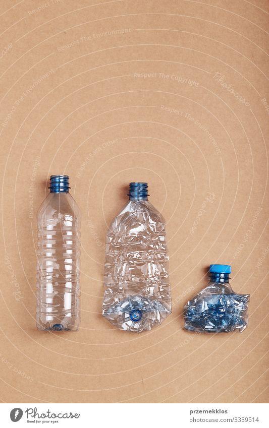 Zerquetschte leere Plastikflaschen in eine Reihe gestellt Flasche sparen Umwelt Container Papier Verpackung Paket Kunststoffverpackung blau Desaster