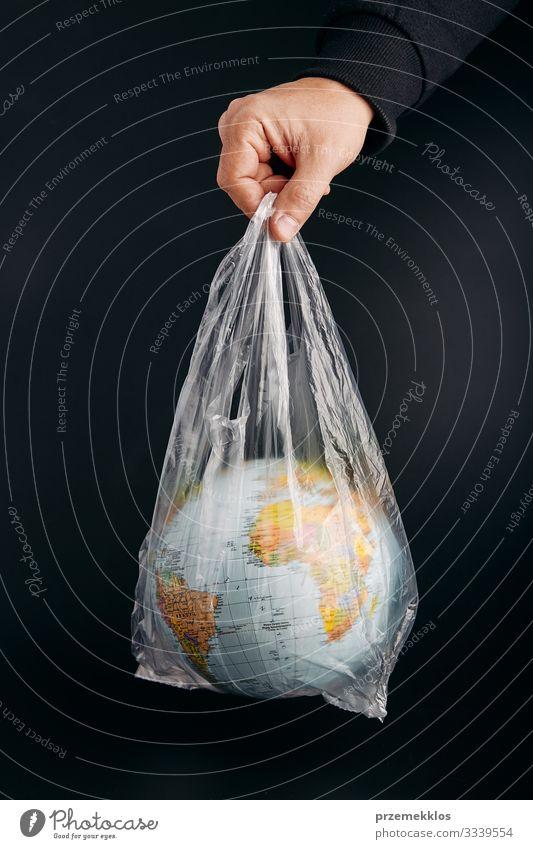 Männliche Hand hält den Globus in einer Plastiktüte. Kontaminierte Erde sparen Leben Mann Erwachsene Umwelt Kunststoff Kugel grün schwarz Umweltverschmutzung