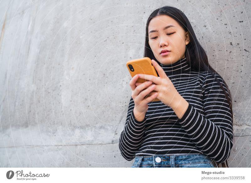 Asiatische Frau, die ihr Mobiltelefon benutzt. Lifestyle schön lesen sprechen Telefon PDA Technik & Technologie Mensch feminin Mädchen Erwachsene 1 18-30 Jahre