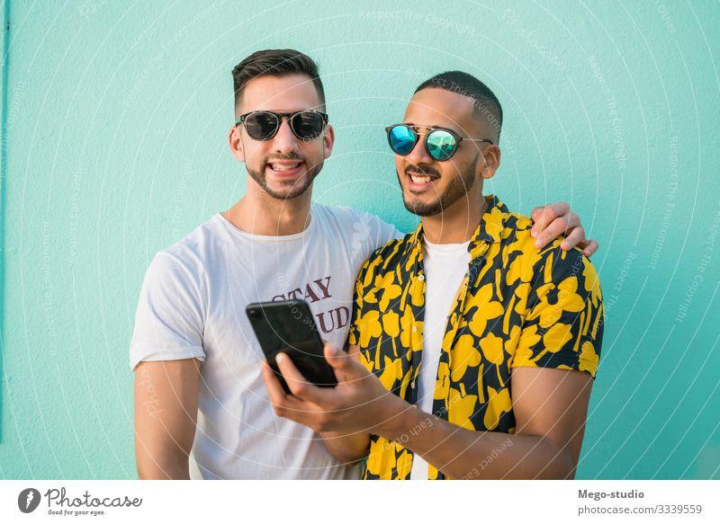 Ein schwules Paar, das Zeit miteinander verbringt, während es telefoniert. Lifestyle Glück Leben Freizeit & Hobby Freiheit Handy PDA Mensch maskulin