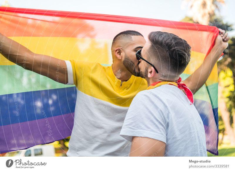 Schwules Paar küsst und zeigt seine Liebe mit der Regenbogenfahne. Lifestyle Glück Freiheit Feste & Feiern Mensch Homosexualität Mann Erwachsene Partner Leben 2