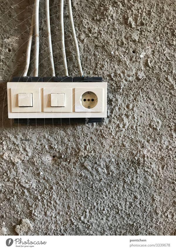Provisorische Steckdose und Lichtschalter auf einer Baustelle. Rohputz Technik & Technologie Energiewirtschaft Energiekrise Armut hässlich kalt