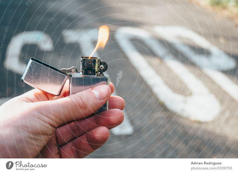 Feuerzeug in der Hand beleuchtet mit Stoppmeldung im Hintergrund Mann Erwachsene Kraft Schutz Geborgenheit gefährlich Gewalt Desaster stoppen Mitteilung