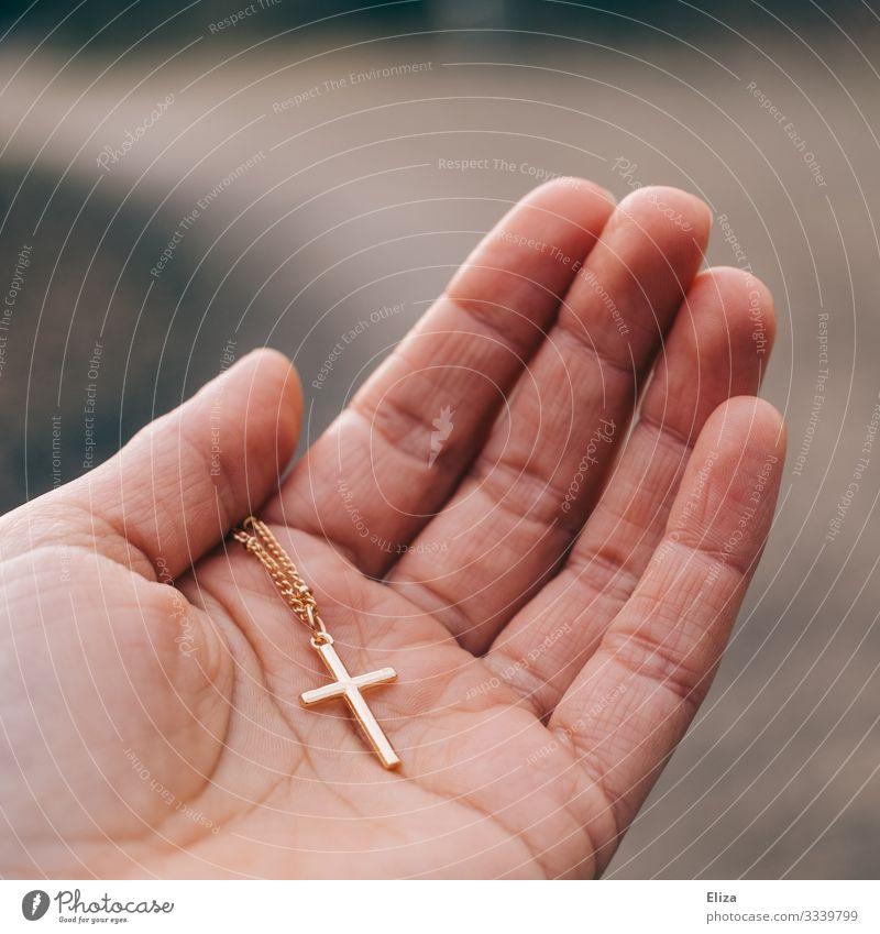Ein goldenes Kreuz an einer Kette, das von einer Hand gehalten wird Mensch 1 Glaube Religion & Glaube Christliches Kreuz Christentum Katholizismus