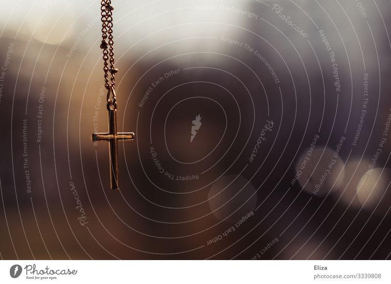 Ein Goldenes Kreuz Kruzifix hängt an einer Kette vor unscharfem Hintergrund in der Kirche Glaube gold Christliches Kreuz Religion & Glaube Christentum