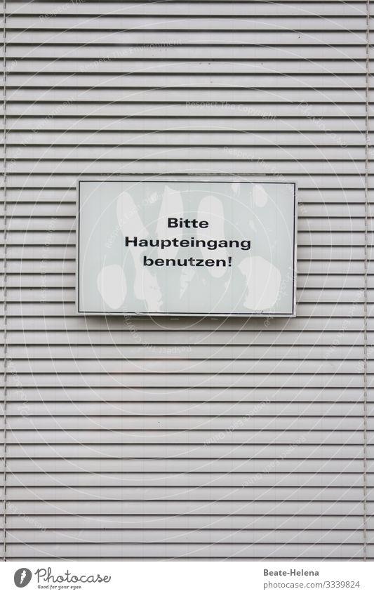 """Druckerzeugnis l Schild """"Bitte Haupteingang benutzen"""" vor quergestreifter Jalousie Hinweisschild Information Aufforderung Schilder & Markierungen Außenaufnahme"""