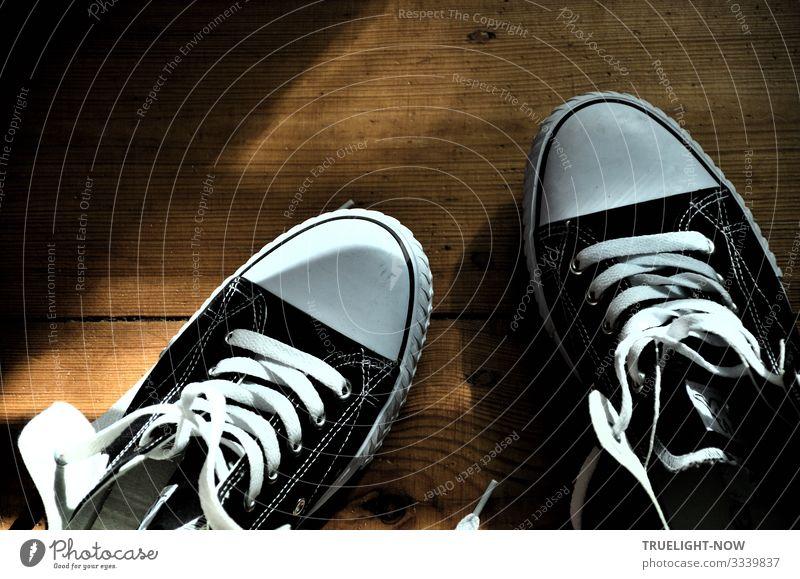 Schwarz-weiße Sneakers auf Holzfußboden mit Sonnenlicht und Schatten Turnschuh Chucks Schuhbänder schwarz-weiss Dielen neu offen locker Farbfoto Innenaufnahme