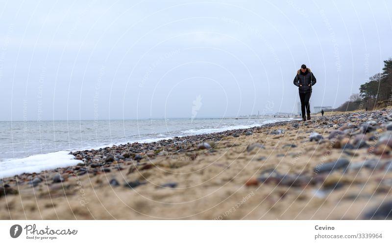 Junger Mann spaziert am Strand Spaziergang Ostsee junger Mann Einsam Einsamkeit Gedanken Urlaub Wellen Steine Sand Wanderung gedankenverloren grübeln