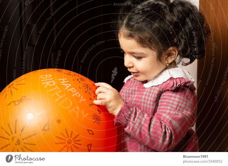 Ein kleines Mädchen spielt mit einem orangenen Geburtstagsballon Lifestyle Design Freude Gesicht Spielen Feste & Feiern Kind Industrie Mensch Kindheit 1