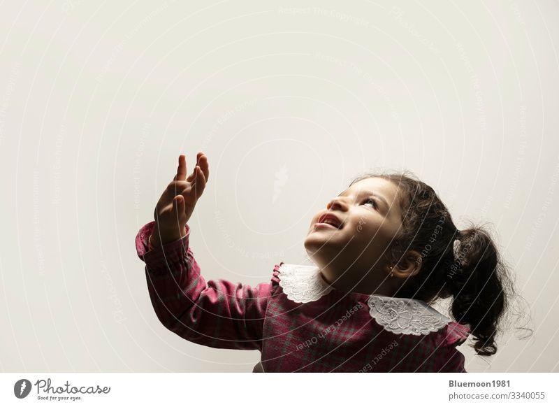 Fröhliches kleines Mädchen mit seitlicher Ponyfrisur im unteren Teil des Bildes mit Blick auf den Rahmen Mittelscheitel-Frisur Seiten-Pony zwei Jahre Pflege