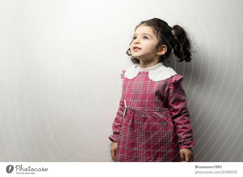 Kleines Mädchen mit seitlicher Ponyfrisur, das aus dem Rahmen schaut Mittelscheitel-Frisur Seiten-Pony zwei Jahre Pflege Gesundheit Porträt kleines Mädchen Mode