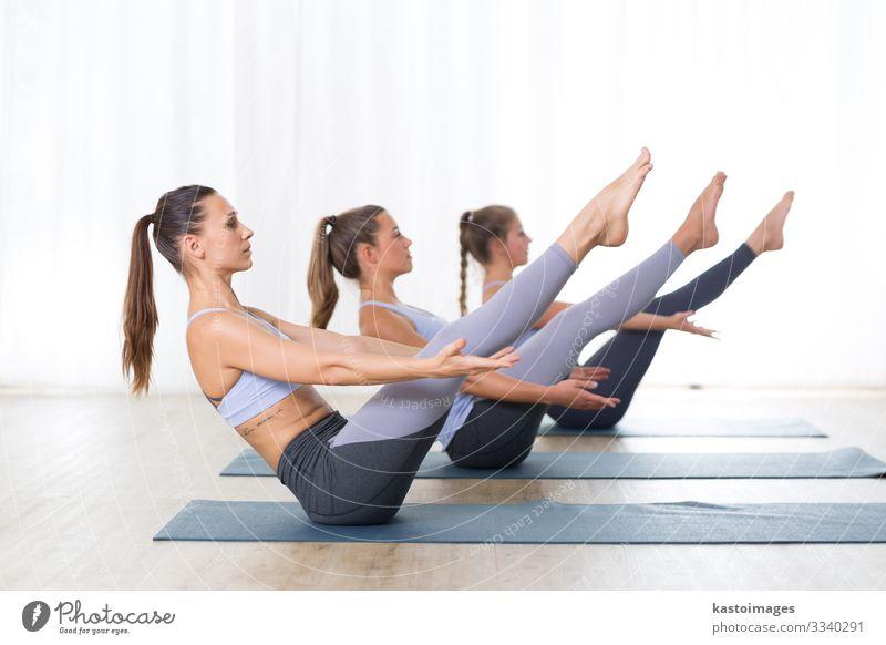Gruppe junger, sportlich attraktiver Frauen im Yogastudio, die zusammen mit dem Ausbilder eine Yogastunde üben, eine Linie in Navasana bilden, Boots-Asana-Yoga-Pose. Gesunder, aktiver Lebensstil, Arbeit im Freien im Fitnessstudio.