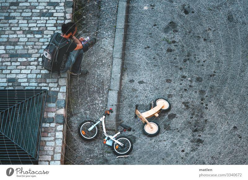 Spielstrasse maskulin 1 Mensch Stadt Verkehrswege Straße liegen sitzen blau gelb grau Kinderfahrrad Asphalt Farbfoto Gedeckte Farben Außenaufnahme