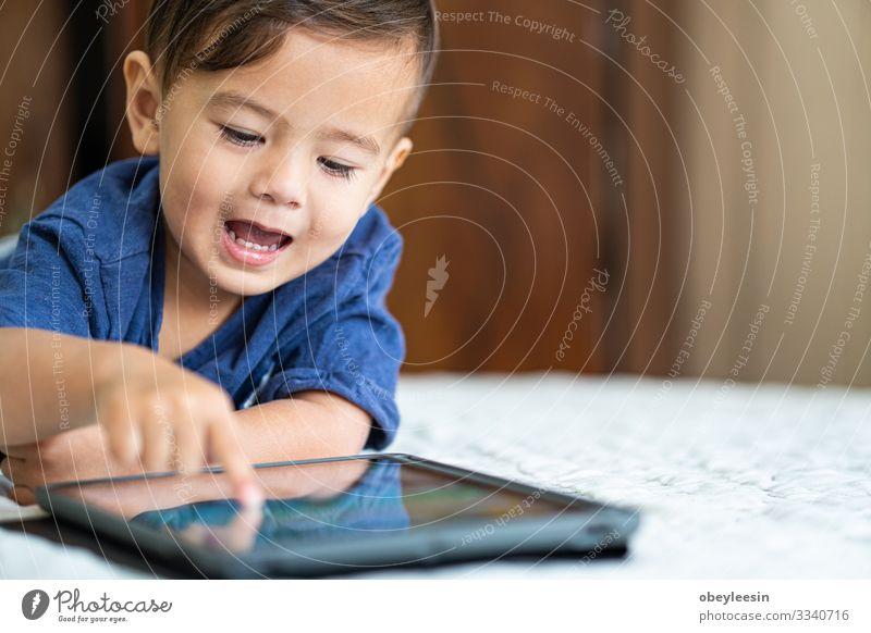 süßer junger Mischlingsjunge, der mit einem elektronischen Gerät spielt Freude Glück Spielen lesen Sommer Garten Schlafzimmer Kind Computer